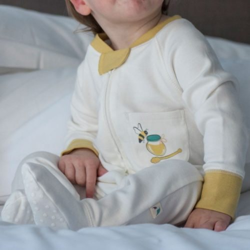 Baby wearing bee graphic sleepsuit