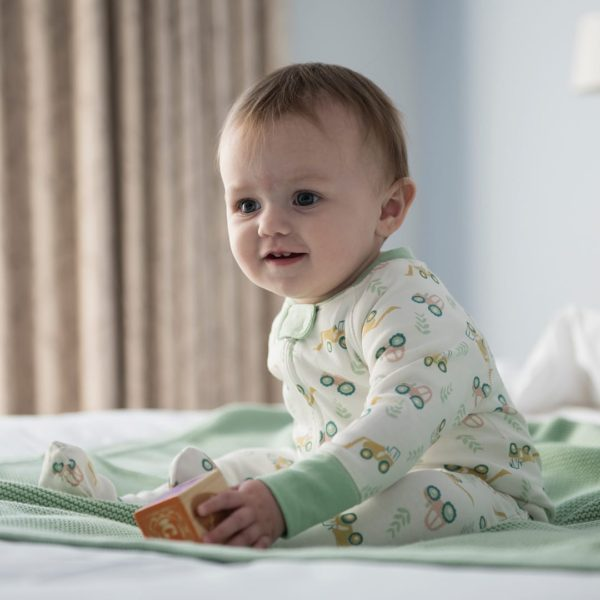 baby boy wearing tractor pattern sleepsuit from Cotton Boulevard